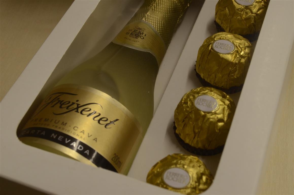 Embalagem em formato de caixa branca com uma garrafa de freixenet e doces ferreiro rocher - dicas de embalagens para vinho